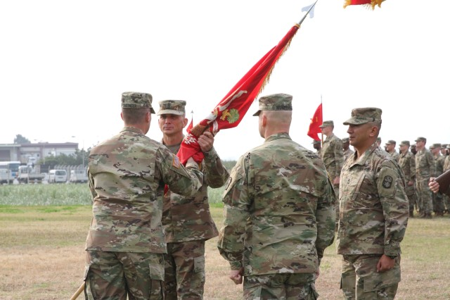 Lt. Col. Scott Dellinger passes the battalion colors to incoming Command Sgt. Maj. Scott Pinkham. The colors symbolize his charge of responsibility for the Soldiers of 1-1 ADA.