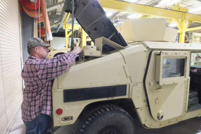 An integrator works on a vehicle in support of Network Integration Evaluation 17.2 in the Build Integration Facility at Fort Campbell, Kentucky, as a part of the Vehicle Platform Integration Design efforts.