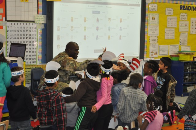 "On March 2, Dr. Seuss's birthday, nineteen Army Contracting Command employees read at Morris Elementary, which is its local adopted school, as part of Read Across America Week. This is the most volunteers that ACC has had in the four years that it has participated in this program.Command Sgt. Maj. Bernard Smalls, of the Expeditionary Contracting Command, read to a kindergarten class. He was all smiles when he heard of their interest in the military, and the reading ended with a round of high fives.But his biggest advice? ""Stay in school and read, read, read!"""
