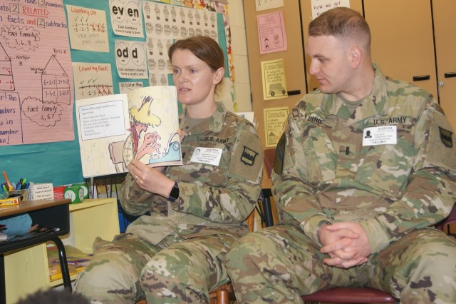 "(Left to right) Capt. Dominique Bogatz reads ""Click Clack Moo, Cows That Type"" while 1st Lt. Chad Bird, both from the 80th Training Command, listens during their visit with children at Hopkins Elementary School in Chesterfield, Va., on March 2, 2017, in honor of Dr. Seuss' birthday and Read Across America Day."