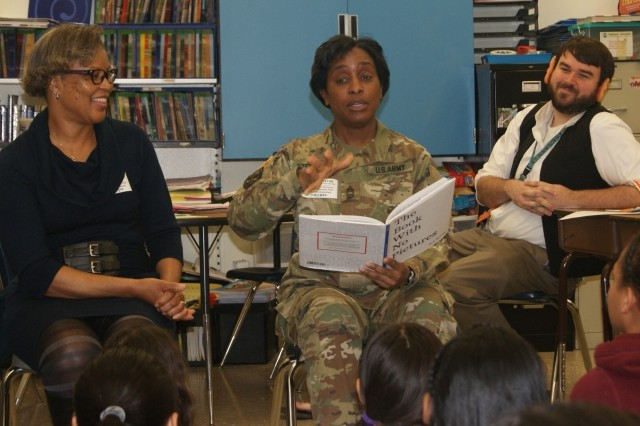 "Mrs. Brenda Dabney (left) laughs while Master Sgt. Monica Stevenson, both from the 80th Training Command, reads ""The Book With No Pictures"" during their visit with children at Hopkins Elementary School in Chesterfield, Va., on March 2, 2017, in honor of Dr. Seuss' birthday and Read Across America Day. (Right) Fourth grade teacher Mr. Kyle Kuzemchak, dressed as the Big Friendly Giant, looks on."