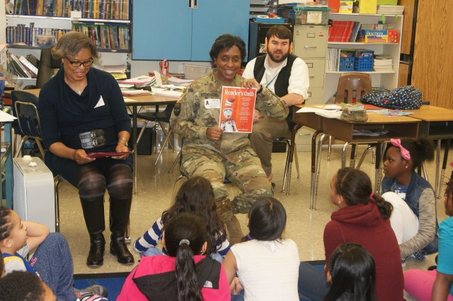 80th Training Command soldiers Mrs. Brenda Dabney (left) and Master Sgt. Monica Stevenson (middle) read the Dr. Seuss Reader's Oath to fourth graders at Hopkins Elementary School in Chesterfield, Va., on March 2, 2017, in honor of Dr. Seuss' birthday and Read Across America Day. Fourth grade teacher Mr. Kyle Kuzemchak (background), dressed as The Big Friendly Giant, enjoys the soldiers visiting his class.