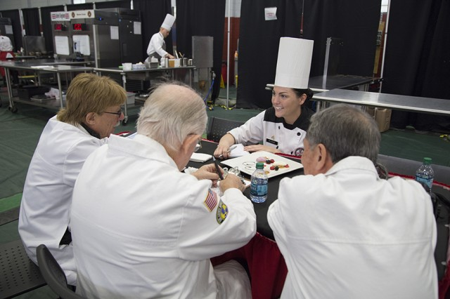 Culinary Specialist Sgt. Melissa Plogar, with Joint Base Langley-Eustis, Virginia, receives her judges critique during the 42nd Annual Military Culinary Arts Competition and Training Event, held at Fort Lee, Virginia. The annual MCACTE is the largest American Culinary Federation sanctioned competition in North America which showcases the talents of military chefs from all services and foreign military teams. (Photo by Visual Information Specialist Stefanie Antosh)