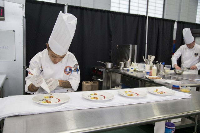 Culinary Specialist Sgt. Erica Larsen plates her dish during the 42nd Annual Military Culinary Arts Competition and Training Event, held at Fort Lee, Virginia. The annual MCACTE is the largest American Culinary Federation sanctioned competition in North America which showcases the talents of military chefs from all services and foreign military teams. (Photo by Visual Information Specialist Stefanie Antosh)