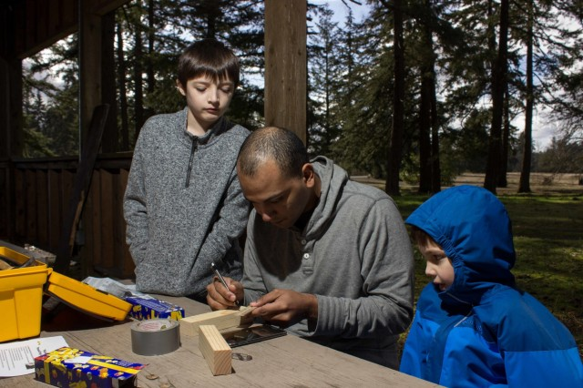 William Lugo (center), a Scouting parent, helps his son Liam Lugo (left), a Webelos Scout, and neighbor's son Dominic Morris (right), a Tiger Scout, get their pinewood blocks ready for cutting at the first of two Derby Garage's hosted by Pack 462, Feb. 11, 2016. The leaders of Pack 462 have donated their time, tools and equipment allowing these boys and their families the opportunity to use these tools that they otherwise would not. (U.S. Army photo by Sgt. David N. Beckstrom, 5th Mobile Public Affairs Detachment, I Corps)