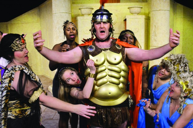 """A group of fawning courtesans surround """"Captain Miles Glorious,"""" played by Sgt. First Class Dan Galvin, during the Caserma Ederle Soldiers' Theatre production of """"A Funny Thing Happened on the Way to the Forum."""" More than 30 volunteers are involved in the show, which includes Soldiers, civilians, family members and local nationals."""