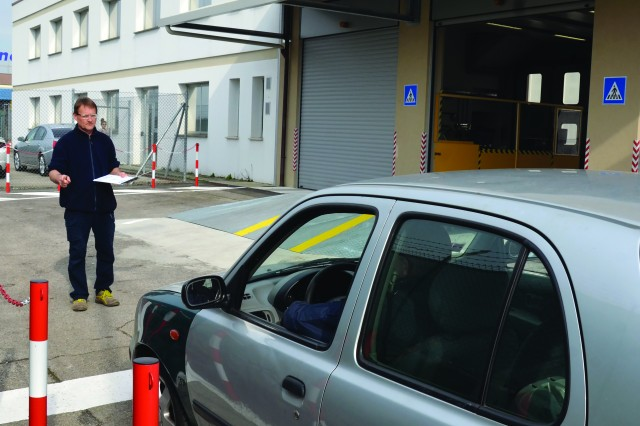 Local national employee Luca Miurizio checks to make sure all the lights are working properly during a vehicle inspection March 6 at the new vehicle inspection point.
