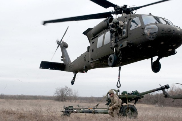 Master Sgt. Richard Harp of the Oklahoma Army National Guard and a member of Headquarters Battery, 1st Battalion, 160th Field Artillery Regiment, 45th Infantry Brigade Combat Team, dismounts a Howitzer after attaching it to a Blackhawk from 1st Battalion, 244th Aviation Regiment, 90th Troop Command, Oklahoma Army National Guard, during an air assault training mission Saturday, March 4, 2017, at Fort Sill in Lawton, Oklahoma.