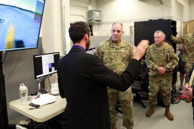 Gen. Gus Perna, commanding general of the U.S. Army Materiel Command, receives briefings from U.S. Army Aviation and Missile Research, Development, and Engineering Center employee, Greg Reynolds with Navigation Lab during his March 9 visit to AMRDEC.