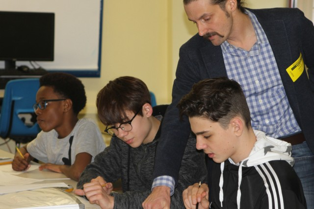 Rich Gifaldi, Europe District, U.S. Army Corps of Engineers, Sustainable Design manager, checks the work of Wiesbaden Middle School students during a solar photovoltaic exercise to determine whether solar panels on the new high school would be cost efficient and help the Army meet Net Zero goals. The STEM event was part of National Engineers Week 2017, taking place in classrooms worldwide.