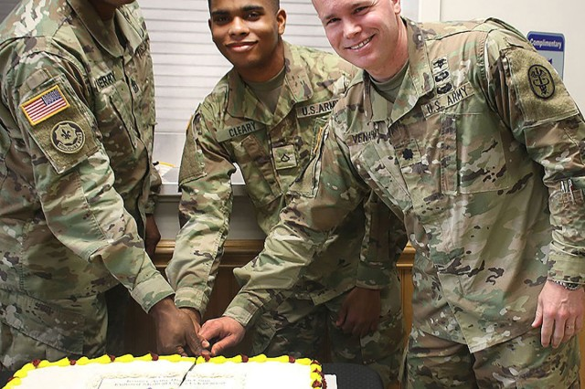 Lt. Col. Brett H. Venable, right, Kenner Army Health Clinic commander, joined by 1st Sgt. Don R. Berry, left, acting facility sergeant major, and Pfc. Andrew Cleary, a pharmacy technician and the youngest enlisted Soldier on the clinic's staff, at a cake-cutting ceremony in recognition of the 130th anniversary of the Army Enlisted Medical Corps March 1 in the Kenner's first floor break room.