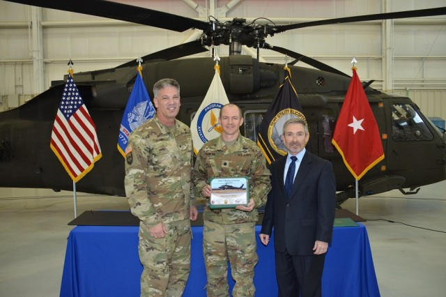 From left, Redstone Test Center's Commander Col. John Jones, Utility Helicopter UH-60V Product Manager Lt. Col Andy Duus and Prototype Integration Facility's Manager Danny Featherson commemorate the official handover of the first UH-60V Black Hawk prototype helicopter to the Army, March 8. The aircraft was transferred from the PIF to the Utility Helicopter Project Office, which then turned it over to the Redstone Test Center to complete developmental testing.