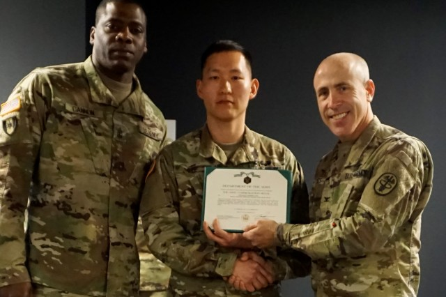 Spc. Anthony Lee (center) is presented with the Army Commendation Medal by Col. Michael Roberts (right), commander of Dental Health Command - Central Region.  Lee recently won the title Soldier Best Warrior during the DHC-Central Best Warrior Competition held at Camp Bullis, Texas.