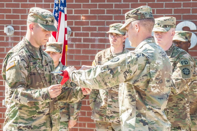 Capt. Shawn Jones, Headquarters and Headquarters Company and 562nd Firefighter Detachment commander, right, cases the colors with Sgt. Mark Banks, during a deployment ceremony March 9 in Sapper Memorial Grove. The 562nd are deploying in support of Operation Inherent Resolve.