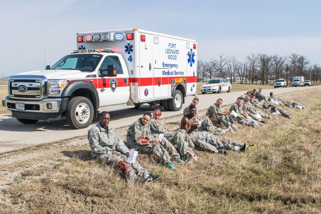 Soldiers await transport following their initial injury assessment during a post-wide exercise March 8