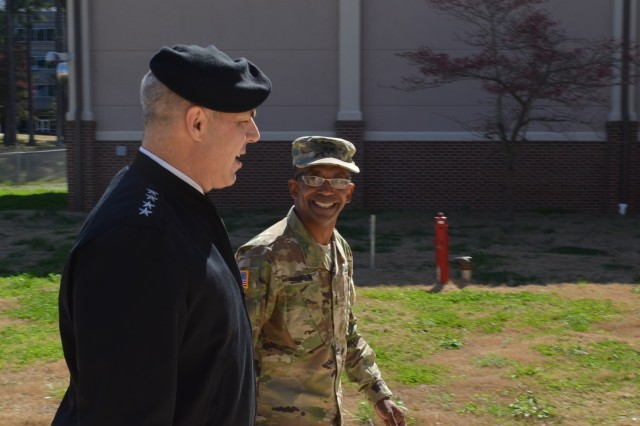 Gen. Gustave Perna, Army Materiel Command commander, and Maj. Gen. James Simpson, Army Contracting Command commander, share a lighter moment as they enter the ACC headquarters building, Redstone Arsenal, Alabama. Perna visited the command for a contracting update.