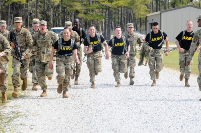 AIT Soldiers run the final leg of the ruck march portion of the AIT Warrior Challenge competition as they're cheered on by fellow Soldiers March 11.