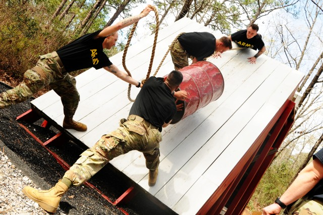 AIT Warrior Challenge competitors work together to complete an obstacle at the Leaders Reaction Course March 11.