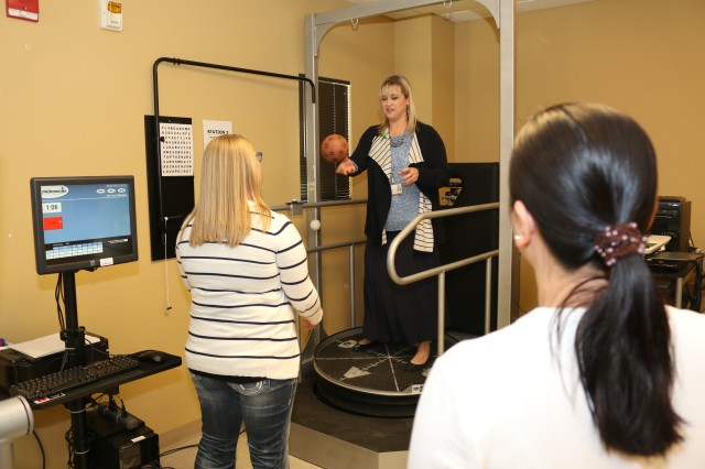 During the Warrior Recovery Center's Open House for Brain Injury Awareness Month a visitor plays catch while standing on a tilting platform.