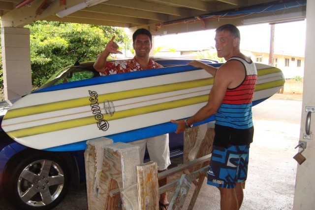 Then Navy Cmdr. Charles Loiselle (right) delivers a new surfboard to Navy Cmdr. Alapaki Gomes in 2014.