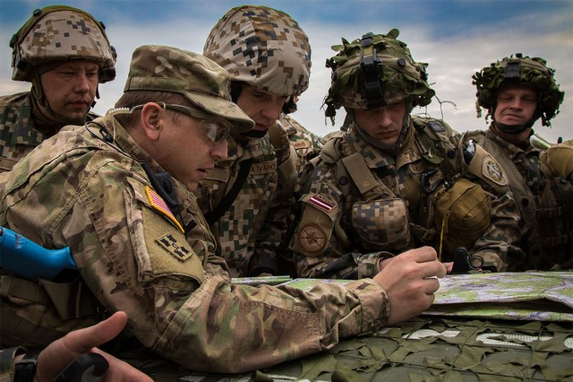 Sgt. 1st Class Andrew Macvey, left, of Joint Multinational Readiness Center (Operations Group) Mustang Observer Coach Training Team mentors Latvian soldiers of the 1st Latvian Brigade. They are conducting a forward recon mission during Exercise Allied Spirit VI at 7th Army Training Command's Hohenfels Training Area, Germany, Mar. 14, 2017. Exercise Allied Spirit VI includes about 2,770 participants from 12 NATO and Partner for Peace nations, and exercises tactical interoperability and tests secure communications within Alliance members and partner nations.
