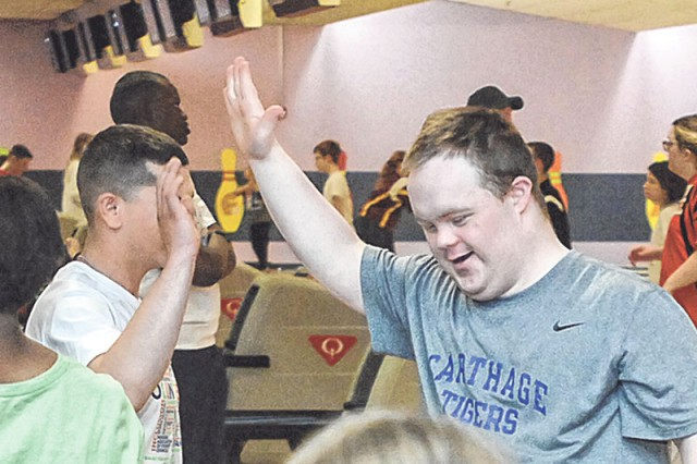 After bowling a strike on Lane 19, Austin Liberty-Acherson, from Carthage, Mo., gets a high five from volunteer Justin Edgmon on Friday during the first day of competition in the Special Olympics Missouri 2017 State Indoor Games at DBC.