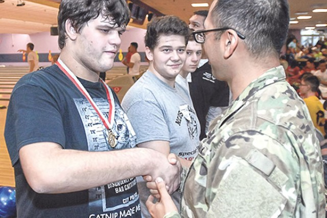 SOMO athlete David Covarrubius, from El Dorado Springs, Mo., shakes hands with Pvt. Miguel Trevino, 84th Chem. Bn., after receiving a gold medal in his division Friday.