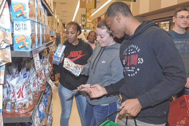 From left: Staff Sgt. Lorena Stevens, Pfc. Priscilla Gibson and Pfc. Bill Marcelin read labels on products at the Commissary Friday. The Soldiers received $75 gift cards to purchase healthy foods at the Commissary.