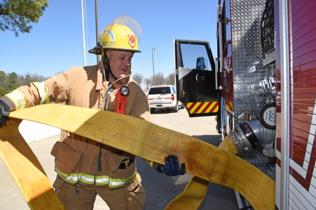 Shawn Johnson, the lead firefighter at McAlester Army Ammunition Plant, Okla., pulls five-inch supply hose to connect to the water hydrant during training. Johnson was recently selected by the U.S. Army Materiel Command as its 2016 AMC Civilian Firefighter of the Year.