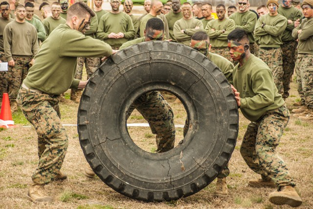 A four-Marine team participates in the tire-flip race during the Engineer Day events Friday.