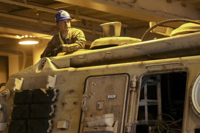 Spc. Julian Chamu, a track vehicle repairer with 2nd Battalion, 7th Cavalry Regiment and native of Santa Anna, Calif., waits further instruction from Soldiers of the 936th Expeditionary Terminal Operating Element, while aboard the of the hull of the large, medium speed, roll on roll off vehicle cargo ship USNS Brittin (T-AKR-305), at the Port of Shuaiba, Kuwait, March 13