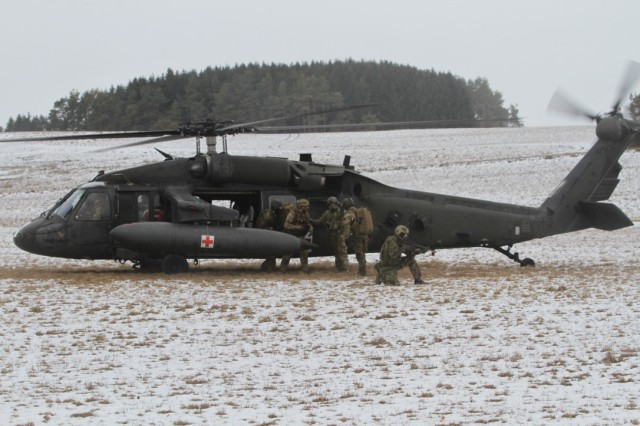 PFULLENDORF, Germany -- A team of multinational NATO and partner nation special operation forces demonstrate the principles of Tactical Combat Casualty Care while loading role-playing casualties onto a UH-60 Black Hawk helicopter during the culminating field training exercise of the NATO Special Operations Combat Medic Course, March 1, 2017. This inaugural class, hosted by the International Special Training Centre, is 22-weeks long and covers not just lifesaving intervention but long-term care to prepare these combat medics to deal with any challenge that may arise on future missions.