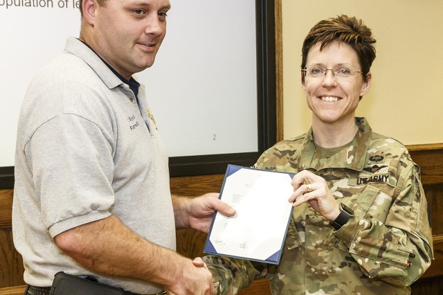 Michael Wood accepts a four-star note from Gen. Gus Perna, commanding general of the Army Materiel Command. Wood earned the title of medical services provider of the year for AMC. Presenting the note is Anniston Army Depot Commander Col. Martine Kidd.