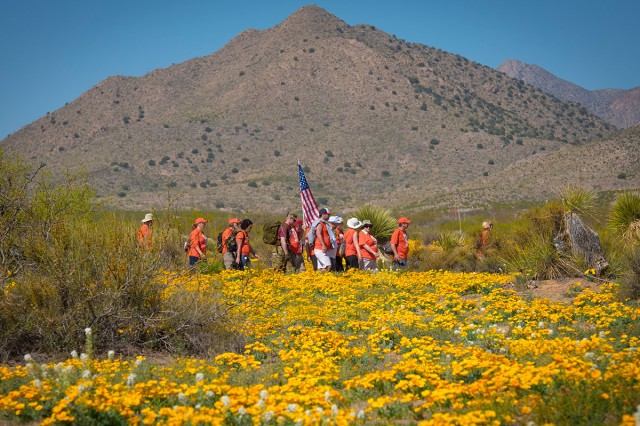"""Retired Col. Ben Skardon, 99 (in white shirt), a survivor of the Bataan Death March, walks through a field of blooming California poppies with members of """"Ben's Brigade"""" - his loyal support team made up of former Clemson University students of his, family, friends and relatives of his fellow WWII prisoners of war - during the Bataan Memorial Death March at White Sands Missile Range, N.M., March 19, 2017. Skardon is the only Bataan survivor who walks in the memorial march, and he walks eight and a half miles. This was his tenth time doing it."""