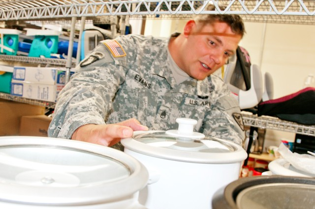 Then-Staff Sgt. Larry Evans, 110th Avn. Bde., borrows some household goods from the Lending Hangar in this file photo.