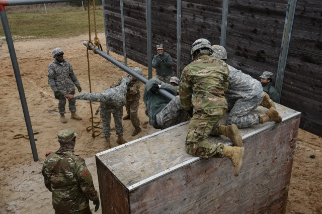 U.S. Soldiers, assigned to Public Health Activity Rheinland-Pfalz, work together during a team-building event at the 7th Army Training Command's Grafenwoehr training area Germany, Mar. 20, 2017. The team-building exercises, which included physical and intellectual features, were designed to build unit morale and camaraderie amongst teams.