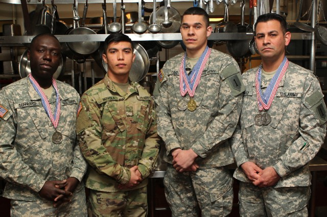 (From left) Spc. Gerald Geffrard, 1st Attack Reconnaissance Battalion, 1st Aviation Regiment, 1st Combat Aviation Brigade, 1st Infantry Division; Pvt. Jeremy Noyola, 2nd General Support Aviation Battalion, 1st Aviation Regiment, 1st CAB; Spc. Carlos O. Cruz, Headquarters and Headquarters Battalion, 1st Inf. Div.; and Warrant Officer Edmund M. Perez Jr., Headquarters and Headquarters Company, 1st CAB, pose March 13 in Fort Riley's Culinary Arts Lab with medals earned at the 42nd Annual Military Culinary Arts Competition at Fort Lee Virginia, March 4-9.  (Chad L. Simon, 1st Inf. Div. Public Affairs)