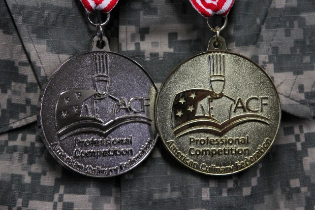 A gold and silver medal hang from the neck of Spc. Carlos O. Cruz, Headquarters and Headquarters Battalion, 1st Infantry Division. Cruz won the medals at the 42nd Annual Military Culinary Arts Competition, Fort Lee, Virginia, March 4-9. (Chad L. Simon, 1st Inf. Div. Public Affairs)