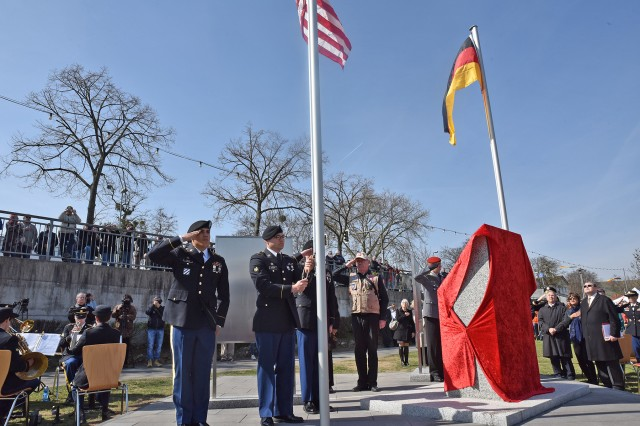 NIERSTEIN, Germany (Mar. 25 2017) -- German and U.S. salute during the playing of the national anthem of each nation as the flags of both countries are raised. A joint German and U.S. Army ceremony here memorialized the historic first Rhine River Crossing of World War II, conducted by the 249th Engineer Combat Battalion under the direction of U.S. Army Gen. George Patton March 23, 1945.  The commemoration featured the unveiling of a monument flanked by German and U.S. flags, static displays of current and historic engineer and amphibious equipment, a flyover of vintage Piper aircraft, a ceremonial crossing of the Rhine and a second dedication ceremony for the Kornsand Nazi Victims Memorial across the Rhine. (Photo by U.S. Army Master Sgt. Crista Mary Mack)
