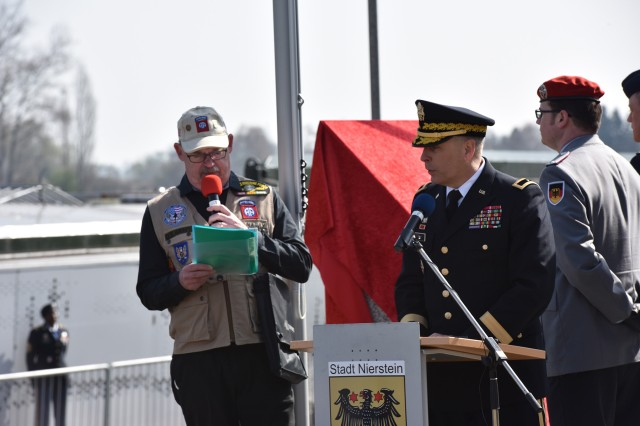 NIERSTEIN, Germany (Mar. 25 2017) -- U.S. Army Europe Brig. Gen. Phillip Jolly, deputy commanding general for Mobilization and Reserve Affairs addresses a crowd of German and U.S. military and civilians at the Nierstein Memorial Ceremony, assisted by an interpreter. A joint German and U.S. Army ceremony here memorialized the historic first Rhine River Crossing of World War II, conducted by the 249th Engineer Combat Battalion under the direction of U.S. Army Gen. George Patton March 23, 1945.  The commemoration featured the unveiling of a monument flanked by German and U.S. flags, static displays of current and historic engineer and amphibious equipment, a flyover of vintage Piper aircraft, a ceremonial crossing of the Rhine and a second dedication ceremony for the Kornsand Nazi Victims Memorial across the Rhine.