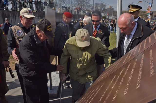 NIERSTEIN, Germany - Two World War II veterans, once enemy soldiers from the Allied (left) and Axis (right)powers, help one another to officially unveil  a memorial dedicated to the bonds between Germany and the U.S. together Mar. 25.