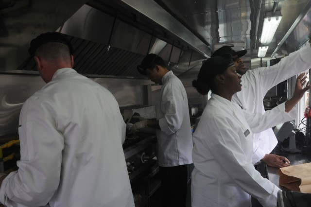 Culinary specialists work together in a food truck at Fort Stewart, Ga., March 24, to serve more than a hundred Soldiers outside the Marne Reception Center. The Soldiers in this truck were serving burgers and rice bowls, made to order, along with sides, salads and drinks. The Army food truck program is part of a larger feeding concept meant to improve food quality and choices for Soldiers across the entire Army. (U.S. Army photo by Sgt. 1st Class Ben K. Navratil)