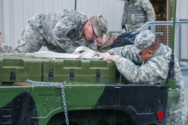 Soldiers from Headquarters and Headquarters Company, 301st Maneuver Enhancement Brigade, prepare a truck to carry cargo before a convoy departs at Joint Base Lewis-McChord, Washington, March 11, 2017. Soldiers from the 301st Maneuver Enhancement Brigade went through a series of maneuver and mobility exercises to ensure deployment readiness and demonstrate the brigade's ability to command and control in a tactical environment. (U.S. Army Reserve Photo by Spc. Sean F. Harding/Released).