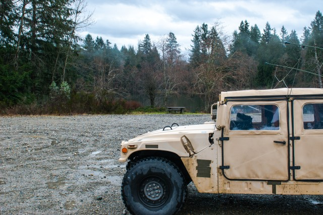 A high mobility multipurpose wheeled vehicle (HMMWV) sits in front of Sequalitchew Lake on Joint Base Lewis-McChord, Washington, March 11, 2017. Soldiers from the 301st Maneuver Enhancement Brigade went through a series of maneuver and mobility exercises to ensure deployment readiness and demonstrate the brigade's ability to command and control in a tactical environment (U.S. Army Reserve photo by Spc. Sean F. Harding/Released).