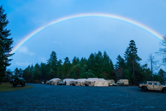 A color spectrum rises above the 301st Maneuver Enhancement Brigade tactical operations center (TOC) on Joint Base Lewis-McChord, Washington, March 11, 2017. Soldiers from the 301st Maneuver Enhancement Brigade went through a series of maneuver and mobility exercises to ensure deployment readiness and demonstrate the brigade's ability to command and control in a tactical environment. (U.S. Army Reserve Photo by Spc. Sean F. Harding/Released).