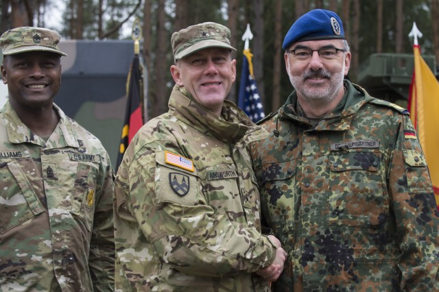 GRAFENWOEHR, Germany -- U.S. Army Brigadier General Steven Ainsworth (center left), Deputy Commanding General of the 21st Theater Sustainment Command, shakes hands with Major General Ulrich Baumgartner (center right), Commanding General of the Bundeswehr Operational Medical Support Command, after signing the first ever memorandum of partnership between the two units during a U.S. Army Europe Expert Field Medical Badge evaluation in Grafenwoehr, Germany on March 24, 2017. Approximately 215 candidates from the U.S. Army and ten European partner nations attended this biannual evaluation in hopes of achieving the coveted U.S. Army EFMB. (U.S. Air Force photo by TSgt Brian Kimball)