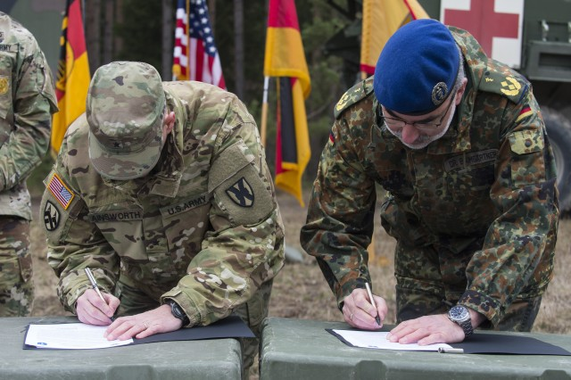 GRAFENWOEHR, Germany -- U.S. Army Brigadier General Steven Ainsworth (left), Deputy Commanding General of the 21st Theater Sustainment Command, and Major General Ulrich Baumgartner (right), Commanding General of the Bundeswehr Operational Medical Support Command, sign the first ever unit memorandum of partnership between the two commands during a U.S. Army Europe Expert Field Medical Badge evaluation in Grafenwoehr, Germany on March 24, 2017. Approximately 215 candidates from the U.S. Army and ten European partner nations attended this biannual evaluation in hopes of achieving the coveted U.S. Army EFMB. (U.S. Air Force photo by TSgt Brian Kimball)