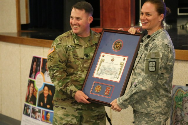Lt. Col. Erik E. Koenig, 36th Signal Battalion commander, presents U.S. Army Reserve Maj. Lisa Jaster with a framed certificate of appreciation. The 36th Signal Battalion, in coordination with the Area IV Equal Opportunity Office, hosted its annual Women's History Month observance at the Camp Henry theater, March 28, 2017.