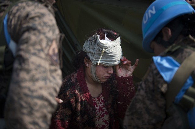 Mongolian soldiers tend to a woman acting as a wounded patient during training at exercise Shanti Prayas III in Nepal. Shanti Prayas is a multinational United Nations peacekeeping exercise designed to provide pre-deployment training to U.N. partner countries in preparation for real-world peacekeeping operations. (U.S. Navy photo by Mass Communication Specialist 2nd Class Taylor Mohr)