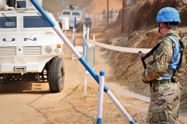 A soldier with the 8th Military Police Brigade provides security as United Nations vehicles pass through a checkpoint during exercise Shanti Prayas III in Nepal. Shanti Prayas is a multinational U.N. peacekeeping exercise designed to provide pre-deployment training to U.N. partner countries in preparation for real-world peacekeeping operations. (U.S. Army photo by Staff Sgt. Michael Behlin)